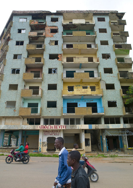 """""""Flats In Huambo after civil war, Angola, 2010. Huambo's name comes from Wambu, one of the 14 old Ovimbundu kingdoms of the central Angolan plateau. In 1928 Huambo was renamed Nova Lisboa (New Lisbon, after Lisbon the capital of Portugal), indicating that the colonial administration had the intention of making it the capital of the colony. After the independence from Portugal in 1975, Nova Lisboa was given back its original name. The Angolan Civil War (1975–2002) stopped Angola's and Huambo's development, destroying an important part of its infrastructure. Huambo became the place of hard battles during the bloody civil war between the government and UNITA from independence, as it UNITA headquarters were located in it, until the death of rebel UNITA leader Jonas Savimbi in 2002. The city was besieged, seriously damaged, and its civilians were slaughtered in crowd or fled the city. The signature of a new cease-fire, after Savimbi's death brought back tranquility to the Province and set the conditions for the current peace process and the beginning of an era of development. Nowadays the city has a population of about 225,000 inhabitants"""". (Eric Lafforgue)"""