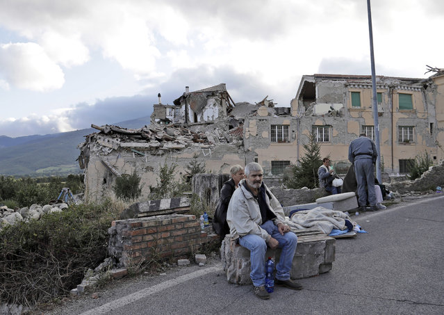 People sit on the side of a road as collapsed buildings are seen in the background following an earthquake, in Amatrice, Italy, Wednesday, August 24, 2016. (Photo by Sandro Perozzi/AP Photo)