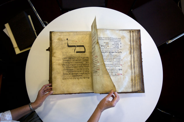 In this photo taken Sunday, October 5, 2014, a library official shows a 13th-century German prayer book containing the earliest evidence of the Yiddish language, at Israel's National Library in Jerusalem. This week, Israel's National Library gave The Associated Press a rare peek at a selection of rare historical manuscripts in its collection. (Photo by Sebastian Scheiner/AP Photo)