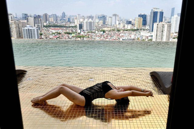 A guest poses for photographs at the infinity pool of the newly-inaugurated Dolce Hanoi Golden Lake hotel, the world's first gold-plated hotel, in Hanoi on July 2, 2020. (Photo by Manan Vatsyayana/AFP Photo)