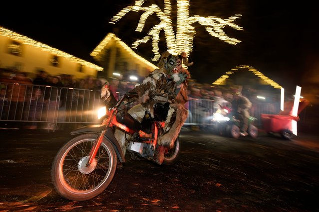 "A participant dressed as a ""Krampus"" creature rides a motorcycle in a parade during ""The Hike of the Krampus of Three Lands"" in the centre of Podkoren, Slovenia on November 24, 2017. (Photo by Jure Makovec/AFP Photo)"