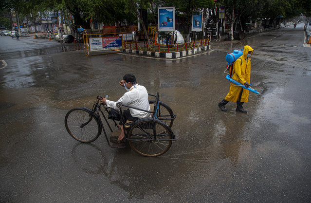 A man rides on a tricycle past a civic worker sanitizing a deserted road during a fresh lockdown imposed in Gauhati, Assam state, India, Sunday, July 12, 2020. India is the world's third worst-affected country by the coronavirus. (Photo by Anupam Nath/AP Photo)