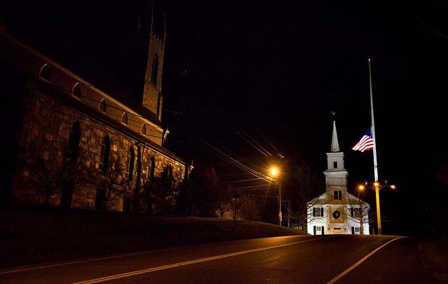 A U.S. flag flies at half-staff on Main Street in Newtown. (Photo by David Goldman/Associated Press)