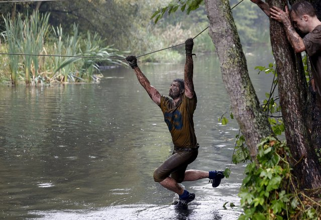 A man crosses a channel on a rope as he takes part in an extreme run competition in Zhodino, east of Minsk, September 26, 2015. (Photo by Vasily Fedosenko/Reuters)