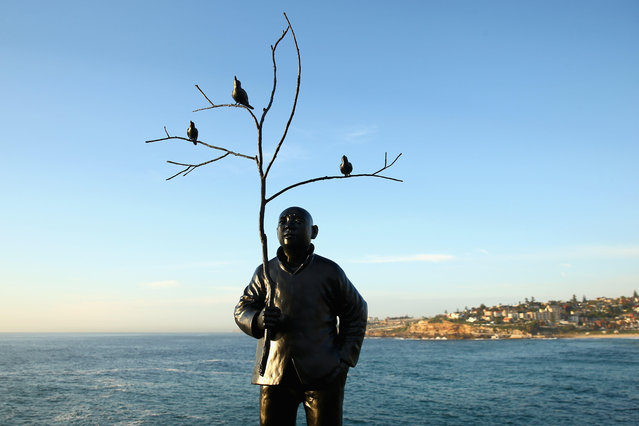 """Men playing with birds"" by Wang Shugang is displayed during the 2014 Sculptures by the Sea exhibition at Tamarama on October 23, 2014 in Sydney, Australia. (Photo by Cameron Spencer/Getty Images)"