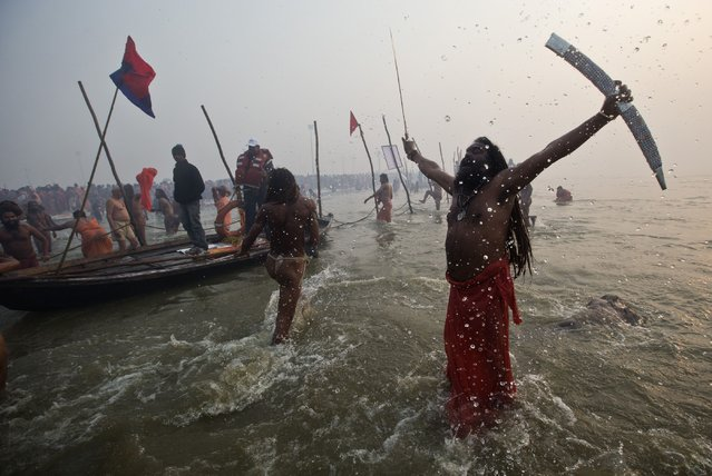 "A Sadhu or a Hindu holy brandishes a sword as he attends the first ""Shahi Snan"" (grand bath) at the ongoing ""Kumbh Mela"", or Pitcher Festival, in the northern Indian city of Allahabad January 14, 2013. Upwards of a million elated Hindu holy men and pilgrims took a bracing plunge in India's sacred Ganges river to wash away lifetimes of sins on Monday, in a raucous start to an ever-growing religious gathering that is already the world's largest. (Photo by Ahmad Masood/Reuters)"