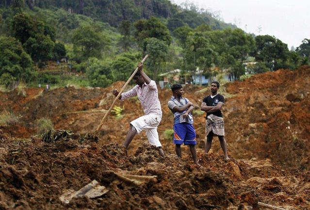 A man searches at the site of a landslide at the Koslanda tea plantation near Haldummulla October 30, 2014. (Photo by Dinuka Liyanawatte/Reuters)