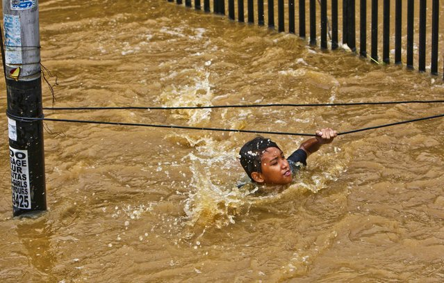 A man grabs wires to keep from being swept away by flood wates in Jakarta, Indonesia, January 18, 2013. Authorities were working to repair a dike that collapsed and flooded  the Indonesian capital. (Photo by Tatan Syuflana/Associated Press)
