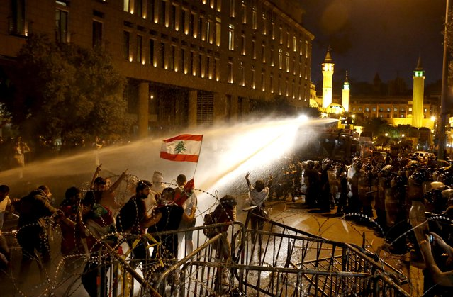 Lebanese protesters are sprayed with water during a protest in Martyr square, Downtown Beirut, Lebanon October 8, 2015. (Photo by Mohamed Azakir/Reuters)
