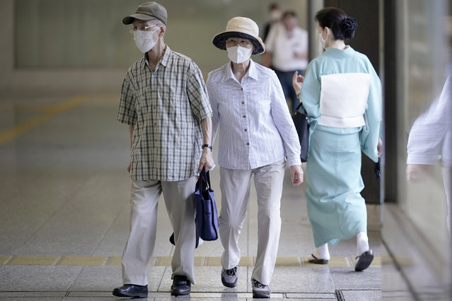 A man and a woman wearing face masks to help curb the spread of the coronavirus walk at an underpass Thursday, August 27, 2020, in Tokyo. (Photo by Eugene Hoshiko/AP Photo)