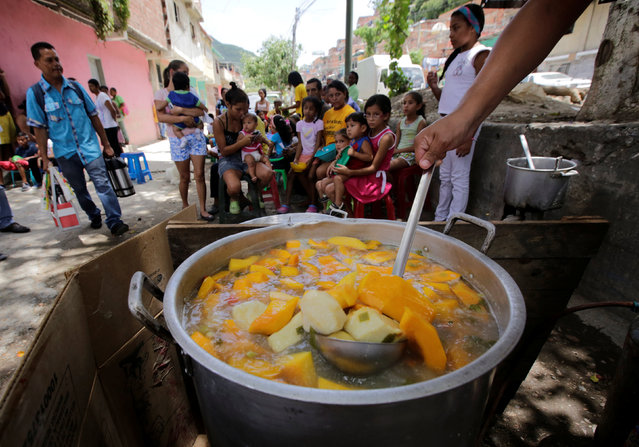 A volunteer prepares food to be distributed for free among residents on a street in the low-income neighborhood of Caucaguita near Caracas, Venezuela September 17, 2016. (Photo by Henry Romero/Reuters)