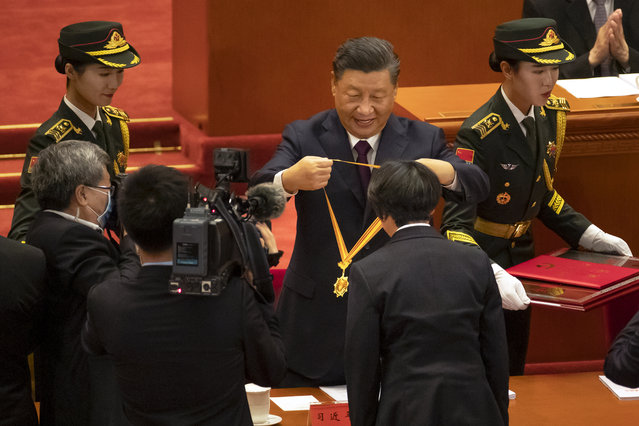 Chinese President Xi Jinping, rear center, presents a medal to an honoree at an event to honor some of those involved in China's fight against COVID-19 at the Great Hall of the People in Beijing, Tuesday, September 8, 2020. (Photo by Mark Schiefelbein/AP Photo)