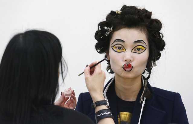 A model has her makeup applied before the Vivienne Westwood Red Label Autumn/Winter 2013 collection presentation during London Fashion Week, February 17, 2013. (Photo by Suzanne Plunkett/Reuters)