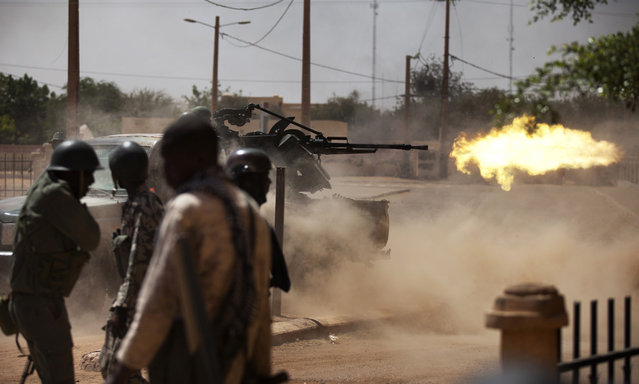 Malian soldiers fire a large weapon in Gao, on February 21, 2013. French and Malian troops fought Islamists on the streets of Gao, as fighting showed little sign of abating weeks before France plans to start withdrawing some forces. (Photo by Joe Penney/Reuters/The Atlantic)