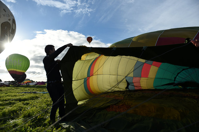 A man begins to inflate his hot air balloon during the Irish hot air ballooning championships in Galway, Ireland September 26, 2016. (Photo by Clodagh Kilcoyne/Reuters)