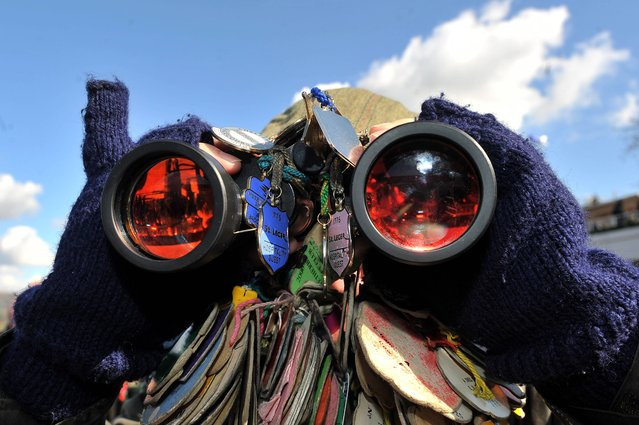 Ian Abbot from Halifax looks through his badge adorned binoculars during St Patrick's Thursday at the 2013 Cheltenham Festival at Cheltenham Racecourse, Gloucestershire, on March 14, 2013. (Photo by Tim Ireland/PA Wire)