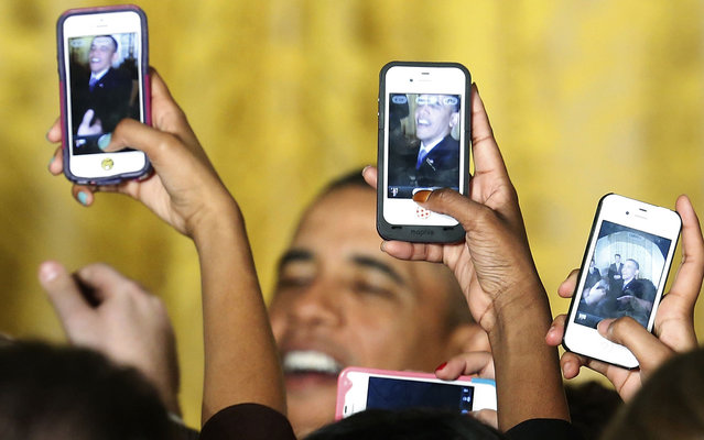 Attendees photograph President Barack Obama with their mobile phones at a Women's History Month reception at the White House in Washington, on March 18, 2013. (Photo by Jonathan Ernst/Reuters)