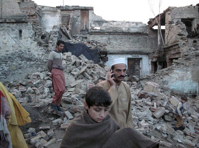 Residents walk past the rubble of a house after it was damaged by an earthquake in Mingora, Swat, Pakistan, October 26, 2015. (Photo by Hazrat Ali Bacha/Reuters)