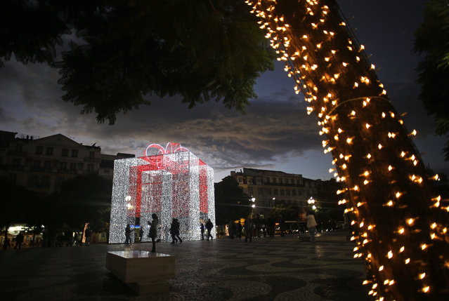 People walk past and take photographs next to a Christmas parcel light decoration at the Rossio square in Lisbon, Thursday, December 4, 2014. (Photo by Francisco Seco/AP Photo)