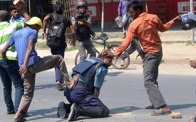 Students wings of Bangladesh Jamaat-e-Islam beat a police officer Jahangir Alam in the northwestern city of Rajshahi, about 260 kms from the capital Dhaka, on April 1, 2013. At least four policemen were injured, one critically, and a firearm and a walkie-talkie were snatched from them when Jamaat-e-Islami activists and its student wing Islami Chhatra Shibir clashed with police in Rajshahi city on Monday morning, local media reported. (Photo by AFP Photo)