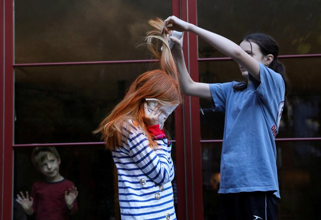 Jane Hassebroek helps her sister Lydia to dye her hair for a Chuckie costume for Halloween at their home, as the coronavirus disease (COVID-19) outbreak continues, in New York, U.S., October 31, 2020. (Photo by Caitlin Ochs/Reuters)