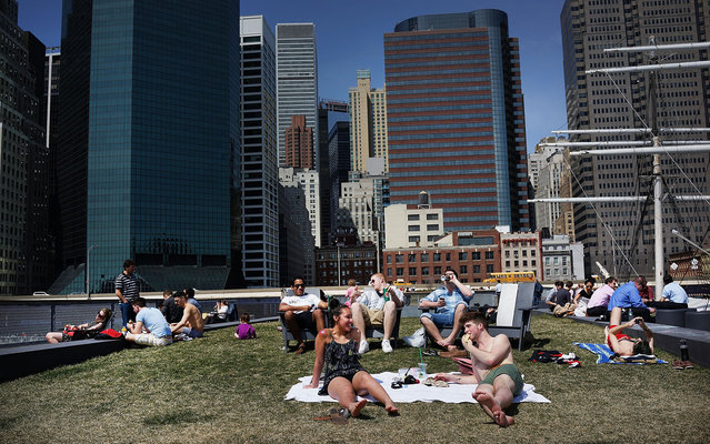 People relax along the East River in lower Manhattan during warm weather on April 9, 2013 in New York City. For the first time since October, temperatures are expected to rise above 70 degrees this week in New York and surrounding areas. (Photo by Spencer Platt/AFP Photo)