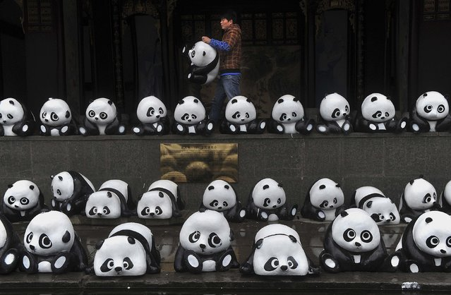 A man moves a panda installation during an exhibition in Hefei, Anhui province, December 10, 2014. (Photo by Reuters/Stringer)