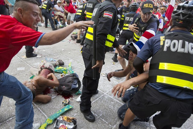 In this July 5, 2014 file photo, a Costa Rica soccer fan is detained by police as another lies on the ground, injured by a knife, after a fight broke out during the live telecast of the quarterfinal World Cup match between Costa Rica and The Netherlands in San Jose, Costa Rica. (Photo by Esteban Felix/AP Photo)