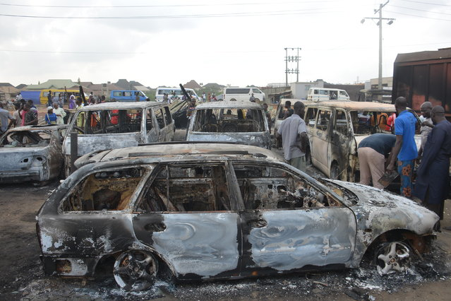 People stand next to burned cars after a tanker exploded on Lagos-Ibadan Expressway on November 7, 2020 in Ogun state killing two people in a huge blaze. Multiple vehicles were engulfed in a fire that started on Saturday morning along the Kara Bridge section of the Lagos-Ibadan Expressway, The incident led to heavy traffic on that section of the expressway on Saturday morning. (Photo by Olukayode Jaiyeola/NurPhoto via Getty Images)
