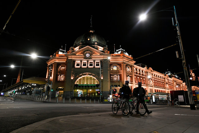 Delivery riders outside Flinders Street Station after a citywide curfew is introduced in Melbourne, Victoria, Australia, 02 August 2020. A state of disaster has been declared in Victoria as the state tightens coronavirus disease (COVID-19) restrictions, limiting movement in Melbourne through a nightly curfew among other new rules. (Photo by Erik Anderson/EPA/EFE)