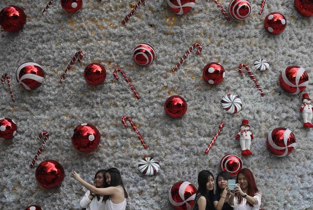 Women take 'selfies' with a Christmas tree outside a mall along Orchard Road in Singapore December 18, 2014. (Photo by Edgar Su/Reuters)