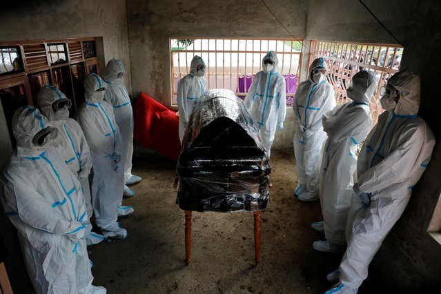 Men dressed in protective suits stand around the coffin of Kenyan doctor Daniel Alushula who died of coronavirus disease (COVID-19), during his funeral in the village of Khumusalaba, in Kakamega county, Kenya on November 13, 2020. (Photo by Baz Ratner/Reuters)