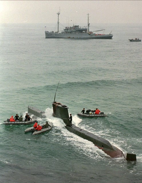 South Korean navy check a North Korean submarine on South Korea's east coast at Kangrung, northeast of Seoul, Thursday, September 19, 1996. South Korean soldiers shot and killed three North Koreans and captured two Thursday, one day after a group of communist infiltrators abandoned their damaged submarine on the rocky coast. (Photo by Ahn Young-joon/AP Photo)