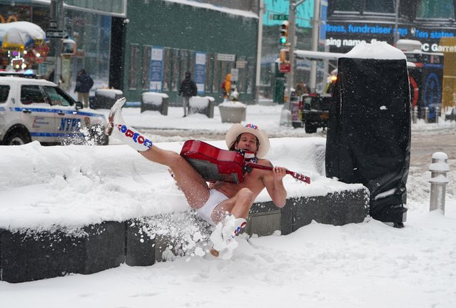"Robert Burck, better known as the ""Naked Cowboy"", falls in the snow during a nor'easter storm in Manhattan, New York City on December 17, 2020. (Photo by Carlo Allegri/Reuters)"