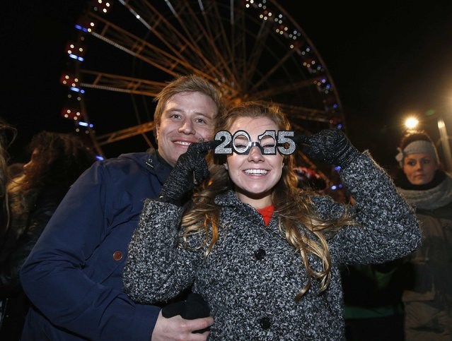 Revellers celebrate the New Year in Princes Street during Hogmanay street party celebrations in Edinburgh, Scotland January 1, 2015. (Photo by Suzanne Plunkett/Reuters)
