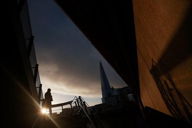 A person walking past The Shard skyscraper is silhouetted as the spread of the coronavirus disease (COVID-19) continues in London, Britain, December 15, 2020. (Photo by Hannah McKay/Reuters)