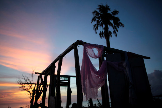 A piece of pink fabric hangs on the remains of a house destroyed by Hurricane Matthew in Roche-a-Bateau, Haiti, October 22, 2016. (Photo by Andres Martinez Casares/Reuters)