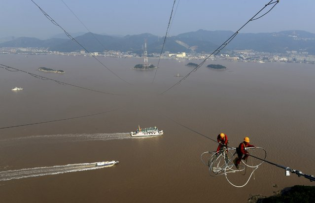 "Boats travel in the sea as workers install components on electricity cables between pylons on an island in Daishan county, Zhejiang province, China, November 2, 2015. China is firmly committed to restructuring and reforms and consumption has ""a lot of room"" to grow, Premier Li Keqiang said on Sunday, dismissing concerns that the economy may be at risk of a hard landing. (Photo by Reuters/China Daily)"