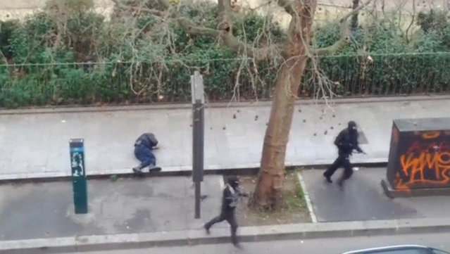 Gunmen flee after shooting a wounded police officer (L) on the ground at point-blank range, outside the offices of French satirical newspaper Charlie Hebdo in Paris, in this still image taken from amateur video shot on January 7, 2015, and obtained by Reuters. (Photo by Reuters/Handout via Reuters TV)