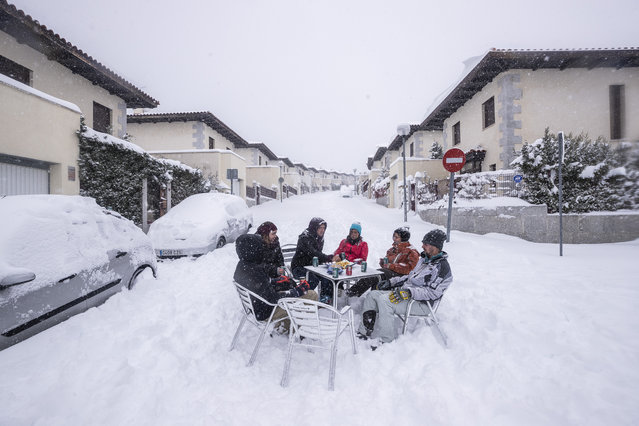 Neighbours have drinks in the middle of the street during a heavy snowfall in Bustarviejo, outskirts of Madrid, Spain, Saturday, January 9, 2021. A persistent blizzard has blanketed large parts of Spain with 50-year record levels of snow, halting traffic and leaving thousands trapped in cars or in train stations and airports that suspended all services as the snow kept falling on Saturday. Half of Spain is on alert, with five provinces on their highest level of warning. (Photo by Bernat Armangue/AP Photo)