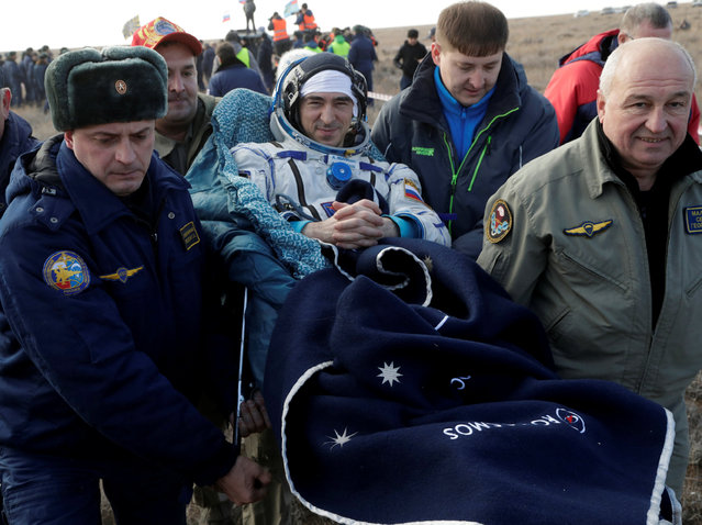 Russian space agency rescue team members carry International Space Station (ISS) crew member Anatoly Ivanishin of Russia shortly after the landing of the Russian Soyuz MS space capsule near the town of Dzhezkazgan (Zhezkazgan), Kazakhstan, October 30, 2016. (Photo by Dmitri Lovetsky/Reuters)