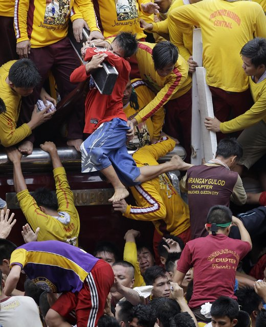 Filipino devotees cling to kiss the cross of the Black Nazarene during a raucous procession to celebrate its feast day Friday, January 9, 2015 in Manila, Philippines. The raucous celebration drew tens of thousands of devotees in a barefoot procession around Manila streets. (Photo by Bullit Marquez/AP Photo)