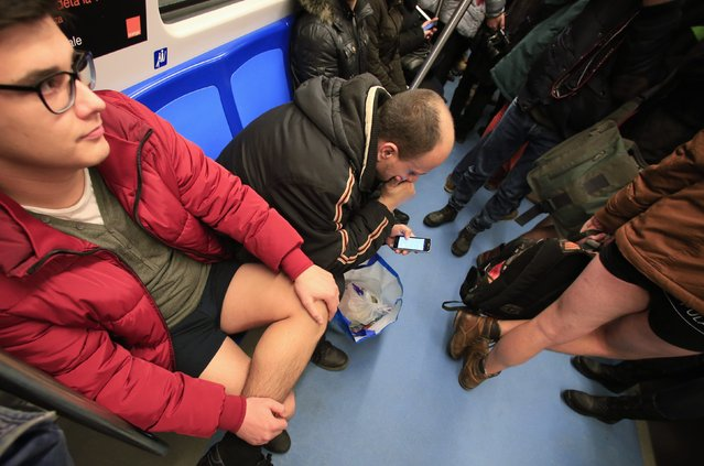 """A man checks his mobile phone between passengers without pants inside a subway train during """"The No Pants Subway Ride"""" in Bucharest January 11, 2015. (Photo by Radu Sigheti/Reuters)"""