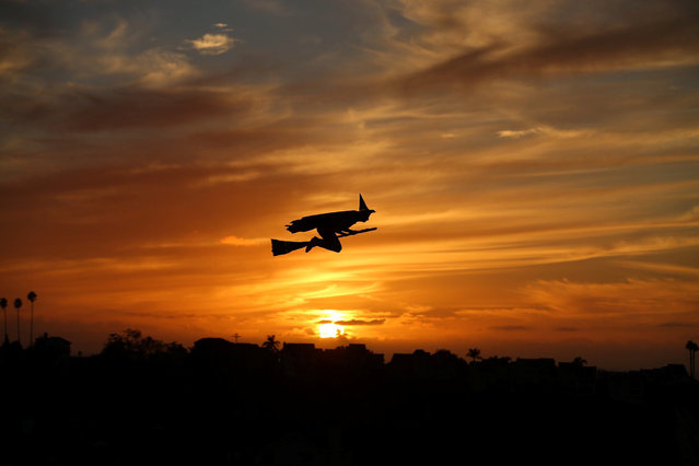 A remote-controlled plane in the form of a witch flies over a neighborhood as the sun sets during Halloween in Encinitas, California, U.S. October 31, 2016. (Photo by Mike Blake/Reuters)