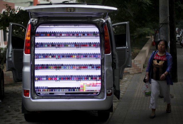 A woman walks past a van which has been converted into a stall selling nail polish on a sidewalk in Beijing, in this June 4, 2013 file photo. (Photo by Barry Huang/Reuters)
