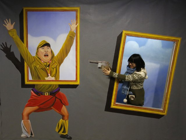 A visitor poses for a photograph in front of a 3D painting depicting a Japanese Imperial army soldier at a 3D art gallery in Beijing January 16, 2015. (Photo by Kim Kyung-Hoon/Reuters)