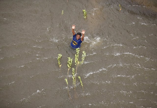 A man stranded in the floodwaters gestures to an Indian coast guard helicopter for relief materials in Chennai, India, December 6, 2015. (Photo by Anindito Mukherjee/Reuters)