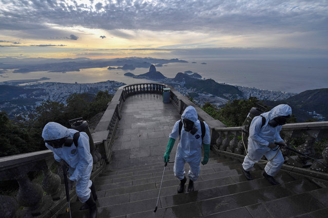 Soldiers of the Brazilian Armed Forces are seen during the disinfection procedures of the Christ The Redeemer statue at the Corcovado mountain prior to the opening of the touristic attraction on August 15, in Rio de Janeiro, Brazil, on August 13, 2020, amid the COVID-19 novel coronavirus pandemic. (Photo by Mauro Pimentel/AFP Photo)