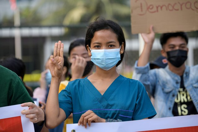 A nurse show the three-finger salute as she takes part in a protest against the military coup and to demand the release of elected leader Aung San Suu Kyi, in Yangon, Myanmar, February 8, 2021. (Photo by Reuters/Stringer)