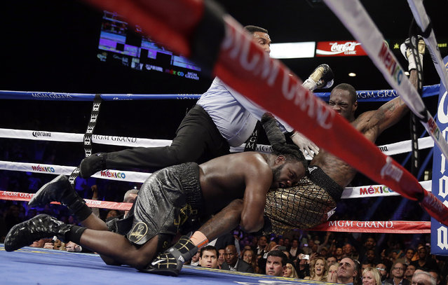 Referee Tony Weeks, left, Deontay Wilder, right, and Bermane Stiverne fall to the mat during the WBC heavyweight championship boxing match Saturday, January 17, 2015, in Las Vegas. (Photo by Isaac Brekken/AP Photo)
